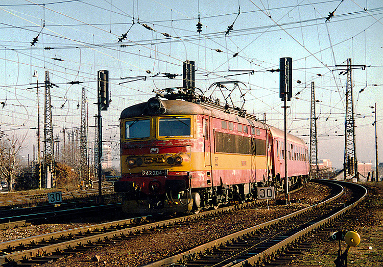 Na nedatovanej snímke, pravdepodobne z jesene 2005, prechádza rušeň 242.204 ešte v unifiku okolo vchodových návestidiel na hlavnú bratislavskú stanicu.