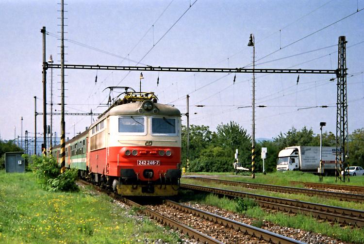 Po šiestich minútach prechádza tým istým miestom plecháč 242.246 s osobným vlakom Os 2013 idúci z Břeclavi cez Bratislavu do Štúrova.