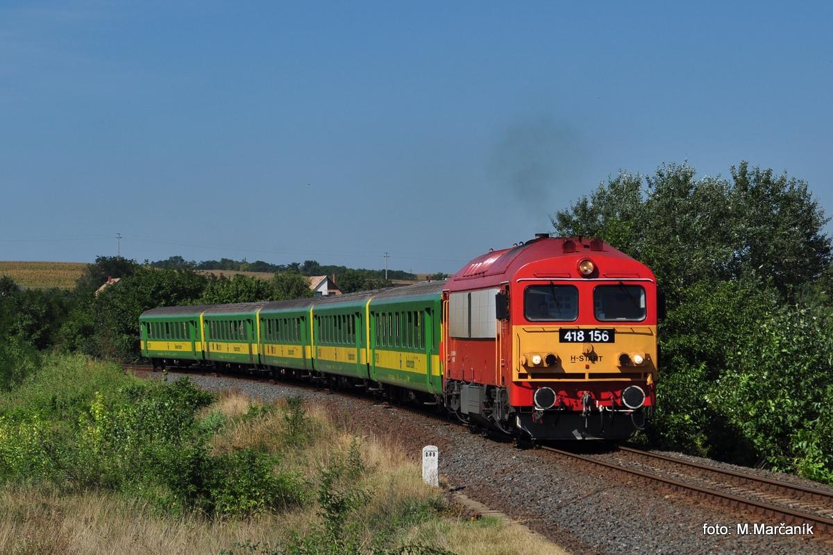 Lokomotiva  418.156 sa představuje v čele vlaku zloženého z vozňov spol. Gysev u žst. Csajág