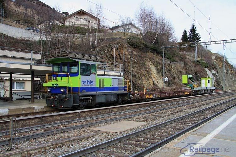 Odstavený pracovný vlak s dvojnápravovým dieselelektrickým rušňom Tm 235 100 upúta pozornosť našinca tým, že je zostavený ako vratná súprava s riadiacim vozňom. Búdka na konci druhého plošinového vozňa je kabína rušňovodiča.