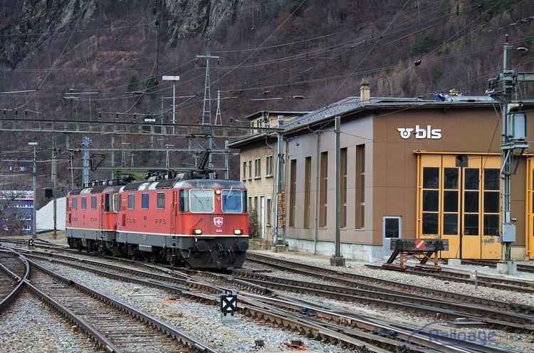 Elektrické rušne SBB Re4/4 11359 + 11313 vchádzajú okolo budovy depa spoločnosti BLS do stanice Brig .