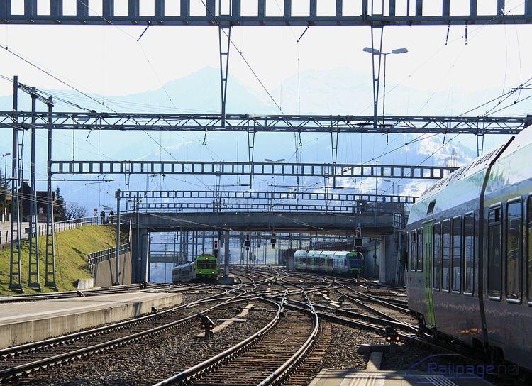 Spiez, 25.februára 2014. Vľavo na strmom stúpaní vchádzala elektrická jednotka RBDe 565 zo smeru Interlaken, v pravej časti snímky je časť jednotky RABe 535 prichádzajúcej z Brigu a v pozadí postávala ďalšia elektrická jednotka rady RABe 535.