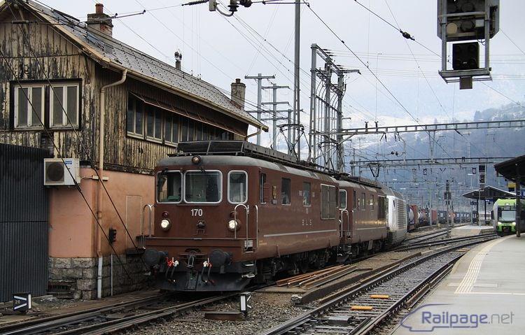 Trojica rušňov (2x Re4/4 + 465) spojených do mnohočlenného riadenia  rozbiehajúc kontajnerový vlak, ktorého trasa povedie cez vrcholový tunel, opúšťa stanicu Brig.