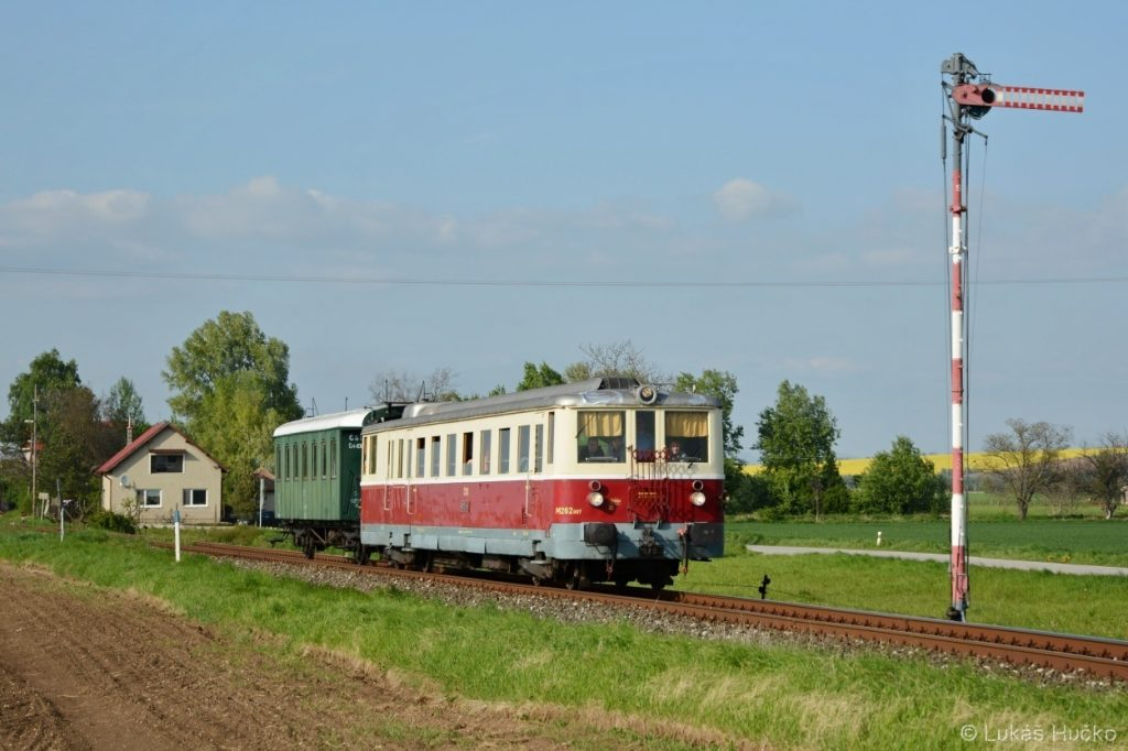 Kolem vjezdového návěstidla stanice Maňa projíždí motorák 830.007
