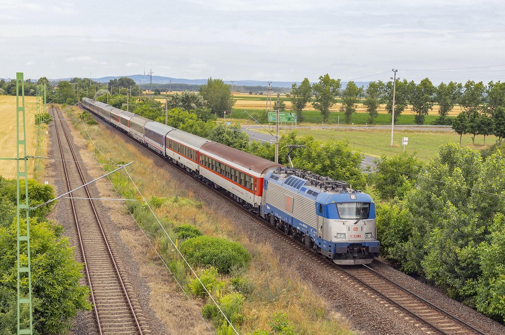 Súprava vlaku EuroNight 477 Metropol ako spoj OsEx 4770 zo stanice Šaľa prichádza do maďarskej pohraničnej stanice Rajka. V pozadí vidno Malé Karpaty a televíznu vežu na Kamzíku.
