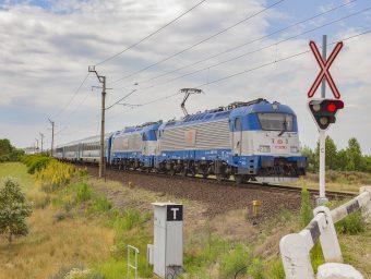 Dva spojené vlaky EC 172 Hungaria a EC 130 Báthory s rušňami 380.010 a 380:009 prechádzajú po jednokoľajnej trati vedúcej z Hegyeshalomu do Rajky.