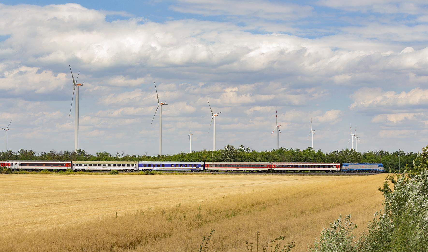 """A znovu tu máme súpravu vlaku EuroNight 477, tentoraz ako dve hodiny zmeškaný vlak EC 275 Metropolitan. Súprava od vlaku EC 275 ostala v Rajke, cestujúci prestúpili do """"EuroNightu"""". Táto snímka je cenná tým, že na nej rušne radu pravidelne 380 ČD nejazdia, ani rad 350 a 362 ZSSK. Snímka je z úseku Hegyeshalom - Mosonmagyarovár na hlavnej trati 1 MÁV."""