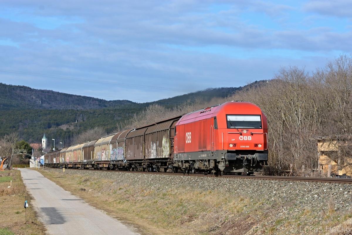 Herkules stoupá s nákladním vlakem nad dálniční nadjezd za stanicí Bad Fischau Brunn dne 06.02.2020