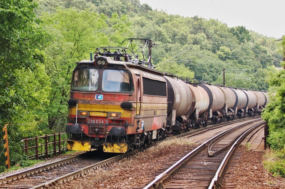 Po Červeném mostě se blíží do zastávky stroj 230.024 se soupravou kotlů dne 07.06.2011
